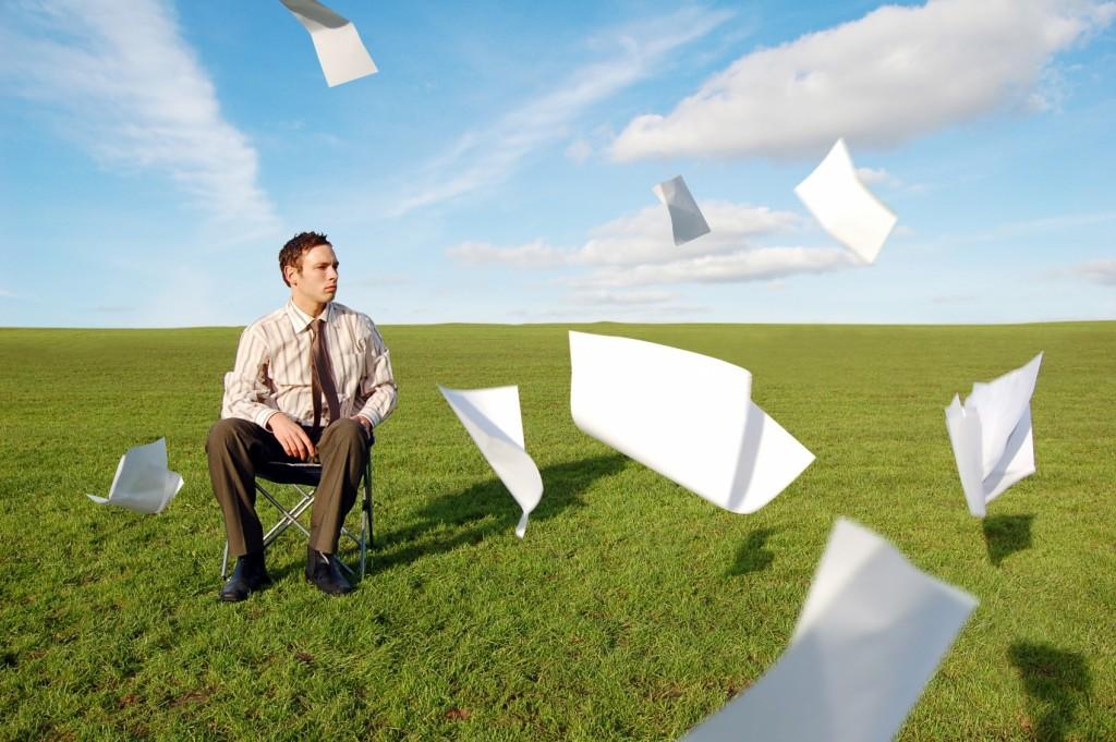 Persona sentada en el campo y papeles volando